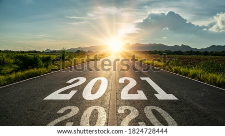 New year 2021 or start straight concept.word 2021 written on the road in the middle of asphalt road at sunset.Concept of planning and challenge or career path,business strategy,opportunity and change #1824728444