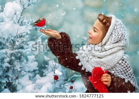 Photo as a postcard in vintage style depicting a small girl in a white downy shawl and red mittens, smiling and feeding a bullfinch bird from her hand, while white fluffy snow is falling around. Royalty-Free Stock Photo #1824777125