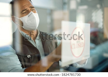 Car repairman with protective face mask hanging closed sign while going out of business due to COVID-19 pandemic. The view is through the glass.