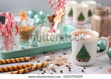 Closeup of Hot Cocoa in a Hot Cocoa Bar with Christmas Cups and Decorations; Multiple Toppings Pictured; White and Gray Countertop