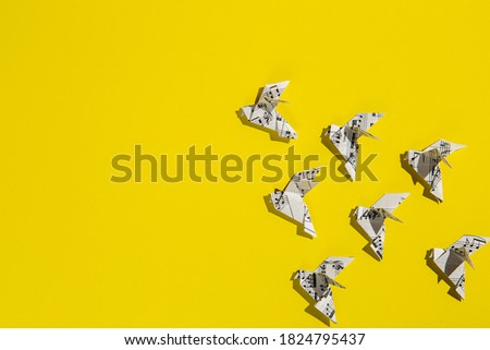 Flock of flying origami doves on yellow background. Origami birds of music paper. Concept of festive music postcard.
