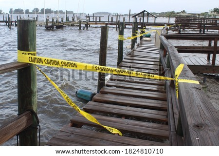 Yellow caution tape blocking off access to a public dock at a local marina due to damage from waves crashing in to the wooden dock boards during a bad storm. Royalty-Free Stock Photo #1824810710