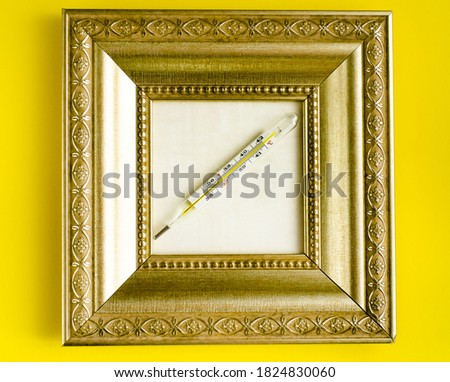 medical mercury thermometer in a gold carved frame on a yellow background.