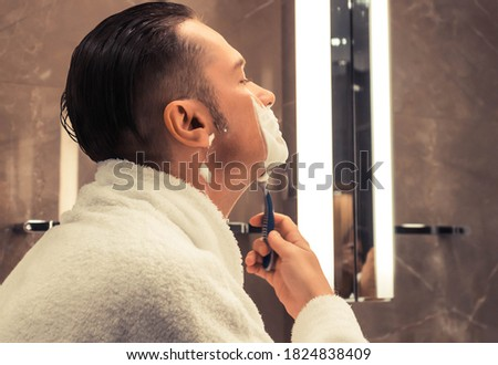 Mid adult man using razor and shaving in the bathroom.  Royalty-Free Stock Photo #1824838409