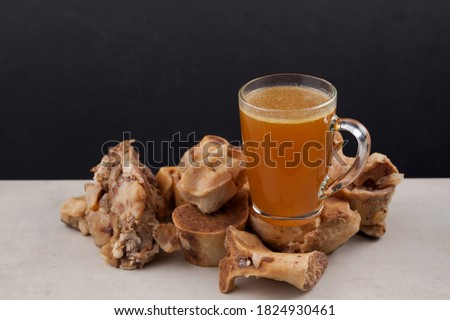 Transparent Cup of bone broth is placed on boiled beef bones, which contain the necessary amino acids for the body. Selective focus Royalty-Free Stock Photo #1824930461