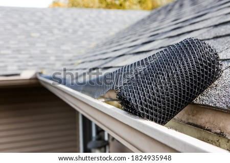 Roll of plastic mesh guard over gutter on a roof to keep it free of leaves, focus on roll of mesh #1824935948