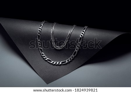 double silver chain necklace on black background with dark and rounded shapes Royalty-Free Stock Photo #1824939821