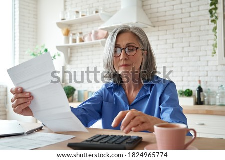 Senior mature business woman holding paper bill using calculator, old lady managing account finance, calculating money budget tax, planning banking loan debt pension payment sit at home kitchen table. Royalty-Free Stock Photo #1824965774