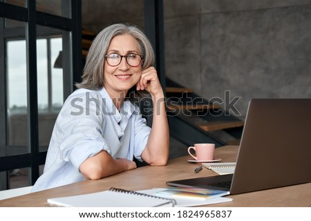 Smiling stylish mature middle aged woman sits at desk with laptop, portrait. Happy older senior businesswoman, 60s grey-haired lady wearing glasses looking at camera sitting at office table. Headshot. Royalty-Free Stock Photo #1824965837