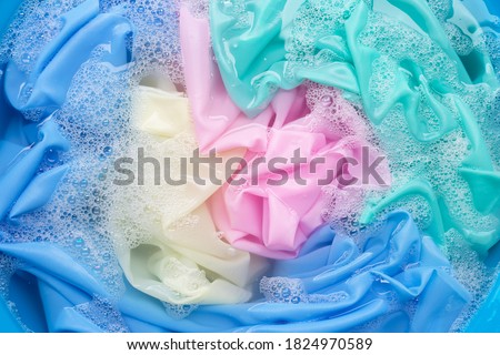 Color clothes soak in powder detergent water dissolution. Laundry concept #1824970589