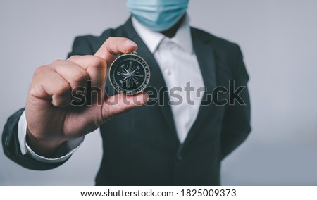 Businessman holding a navigation compass in hand with copy space background. business planning and Business navigate recovery for businessmen to resume business growth in the economic crisis Royalty-Free Stock Photo #1825009373