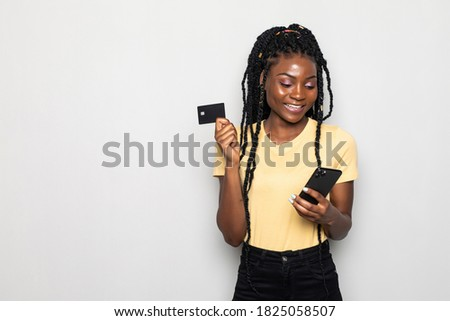 Picture of smiling young african woman standing isolated over white background. Looking aside while using phone and holding debit card.