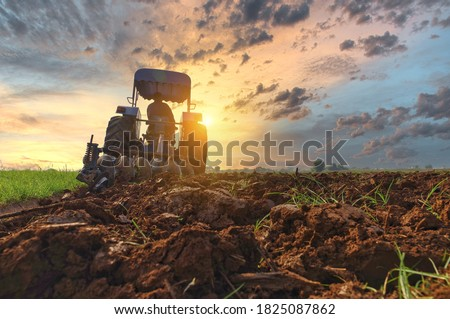 Farmer in tractor preparing land with seedbed cultivator as part of pre seeding activities in early spring season of agricultural works at farmlands Cultivated field Agronomy farming husbandry concept #1825087862