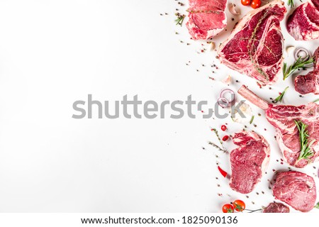 Set of various classic, alternative raw meat, veal beef steaks - chateau mignon, t-bone, tomahawk, striploin, tenderloin, new york steak. Flat lay top view on white table background Royalty-Free Stock Photo #1825090136