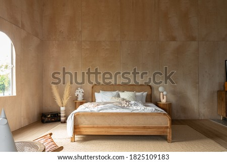 Stylish Bedroom corner with rattan headboard and bed with soft pillows setting with white pillows plywood wall on the background / cozy interior design / modern interior Royalty-Free Stock Photo #1825109183