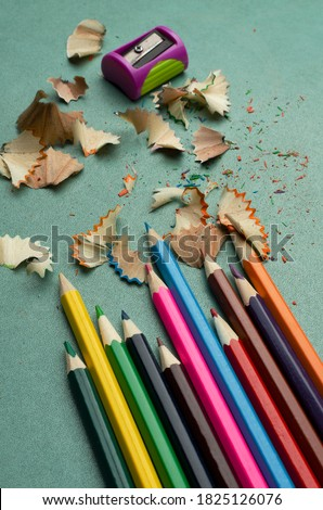 Vertical image.Pencil sharpener, shavings and colored pencils on the bright blue desk