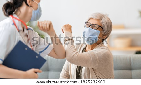 Doctor and senior woman wearing facemasks during coronavirus and flu outbreak. Virus protection. COVID-2019. Taking on masks. Royalty-Free Stock Photo #1825232600