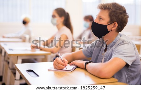 Portrait of teenager in protective face mask writing in workbook on lesson. New life reality during COVID pandemic Royalty-Free Stock Photo #1825259147