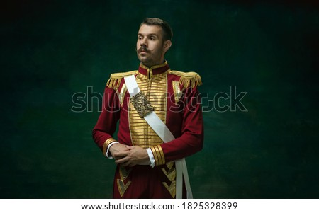 Young man in suit as Nicholas II isolated on dark green background. Retro style, comparison of eras concept. Beautiful male model like historical character, monarch, old-fashioned. Royalty-Free Stock Photo #1825328399