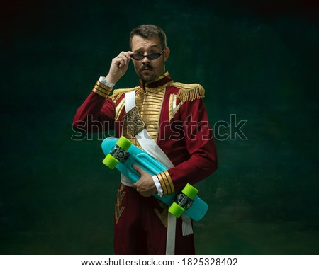 Young man in suit as Nicholas II isolated on dark green background. Retro style, comparison of eras concept. Beautiful male model like historical character, monarch, old-fashioned. Royalty-Free Stock Photo #1825328402
