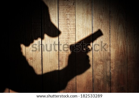 Man in silhouette with gun ready to shoot on natural wooden background, with space for text or image. #182533289