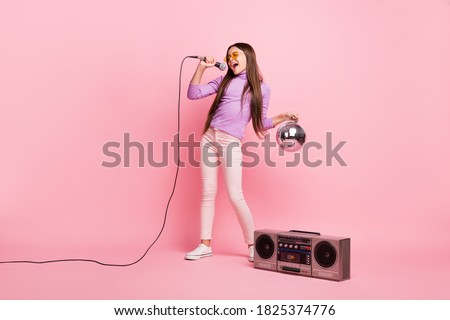 Full length photo of cool small kid girl sing song mic hold disco ball with boom box isolated over pastel color background