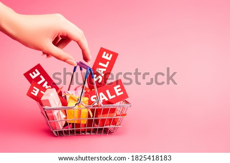 cropped view of female hand near shopping basket with gifts and red tag with lettering on pink, black friday concept Royalty-Free Stock Photo #1825418183