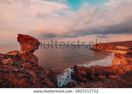 Amazing sunset at sea, beauty of nature. Scenic view of the sea, rocky coastline and sandy beach, golden sky and sun, outdoor travel background. General's beaches. Crimea.