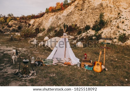 Autumn boho scenery with wigwam and vintage outdoor decor near the mountains.