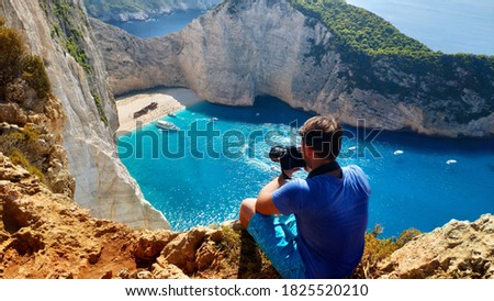 A man photographer with DSLR camera sits on top of a mountain on a cliff overlooking the sea and navayo beach on the island of Zakynthos in Greece
