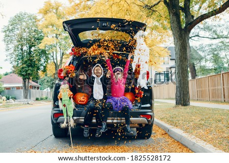 Trick or trunk. Children celebrating Halloween in trunk of car. Boy and girl with red pumpkins celebrating traditional October holiday outdoor. Social distance during coronavirus pandemic. #1825528172