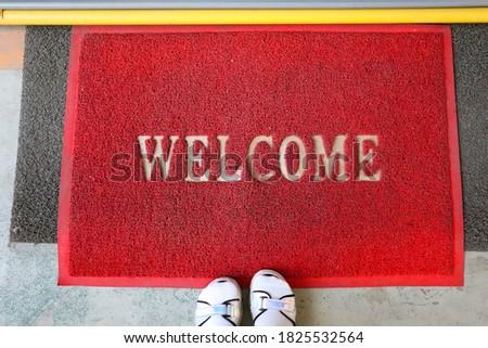 Welcome red mat in front of door, shop. #1825532564