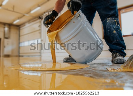 Worker applying a yellow epoxy resin bucket on floor. Royalty-Free Stock Photo #1825562213