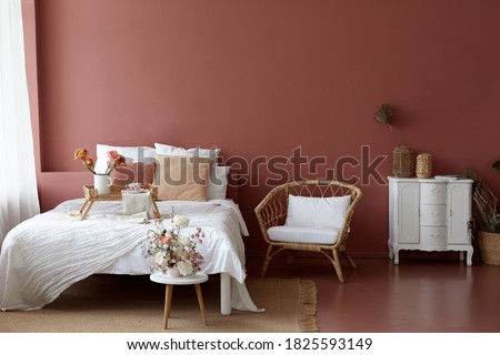 Cozy bedroom interior of retro armchair, vintage chest dwarf and bed on the background of the pink wall and painted wooden floor Royalty-Free Stock Photo #1825593149