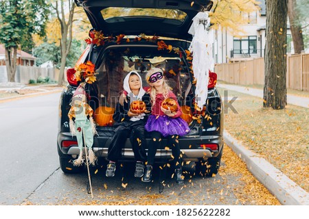 Trick or trunk. Children celebrating Halloween in trunk of car. Boy and girl with red pumpkins celebrating traditional October holiday outdoor. Social distance and safe alternative celebration. #1825622282