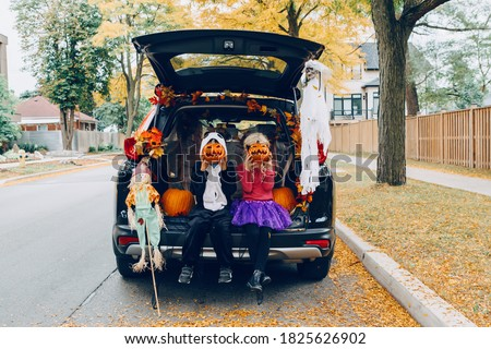 Trick or trunk. Children celebrating Halloween in trunk of car. Boy and girl with red pumpkins celebrating traditional October holiday outdoor. Social distance and safe alternative celebration. #1825626902