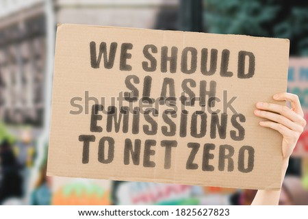 """The phrase """" We should slash emissions to net zero """" on a banner in men's hand with blurred background. Ecology. Industry. Technology. Pollution. CO2. Global warming. Decrease Royalty-Free Stock Photo #1825627823"""
