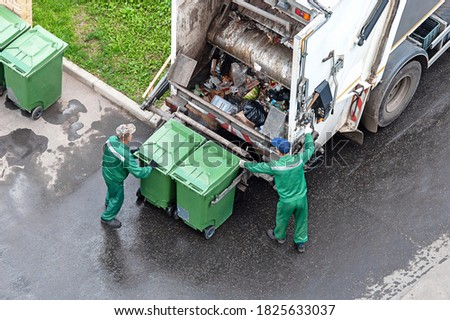 two workers loading mixed domestic waste in waste collection truck Royalty-Free Stock Photo #1825633037