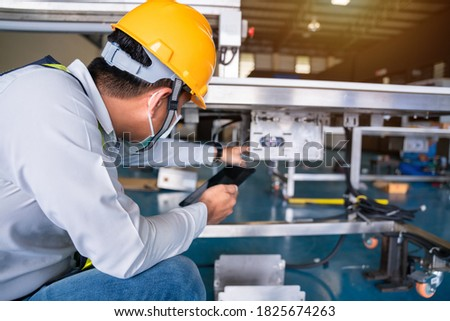 Asian man Mechanic technician worker working install and checking the electric control cabinet of conveyer in industrial factory. Royalty-Free Stock Photo #1825674263
