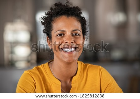 Portrait of a beautiful mid adult woman smiling at home. Middle aged african woman in casual looking at camera with copy space. Cheerful mixed race girl relaxing at home with big laugh.