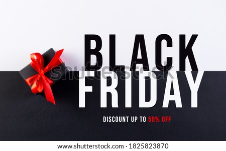 Black Friday. Top view of black christmas boxes with red ribbon on black and white paper background with copy space for text.