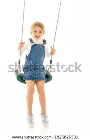 Full Length Shot of Cute Happy Girl Sitting on Rope Swing