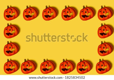 Pattern. On a yellow background, there are many pumpkins with a carved smile. Pumpkins standing in a glad around the perimeter. Free space in the center. Halloween celebration concept.