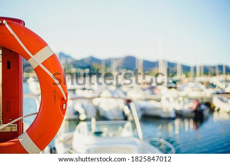 Red lifebuoy photographed up close on a sunny day with a boat harbor and small boats in the background. Royalty-Free Stock Photo #1825847012