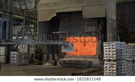 Loader mixing red-hot aluminium in bowl in aluminium plant. Aluminium foundry furnace loaded with metal. Red hot flames glowing and liquid melting. Fire melts aluminum ingots in a blast furnace. #1825851548