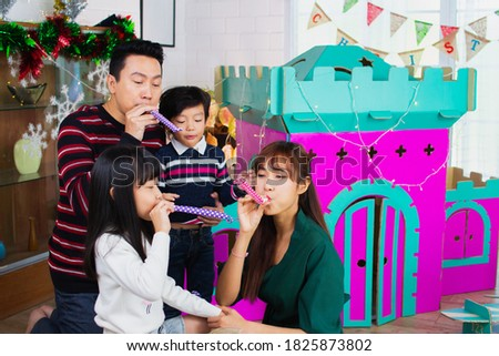 Asian family father, mother, daughter, son blowing party horn blower at party.