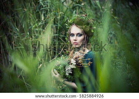 Beautiful fairy witch woman in green grass outdoors. Halloween character or Forest soul Royalty-Free Stock Photo #1825884926