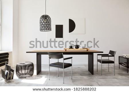Stylish dining room interior with design wooden family table, black chairs, teapot with mug, mock up art paintings on the wall and elegant accessories in modern home decor. Template. Royalty-Free Stock Photo #1825888202