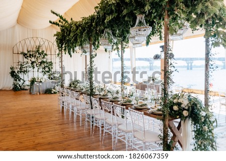 Banquet tables decorated with arrangements of flowers, herbs and candles in the tent. Wedding. Banquet.Crystal chandeliers hang from above Royalty-Free Stock Photo #1826067359