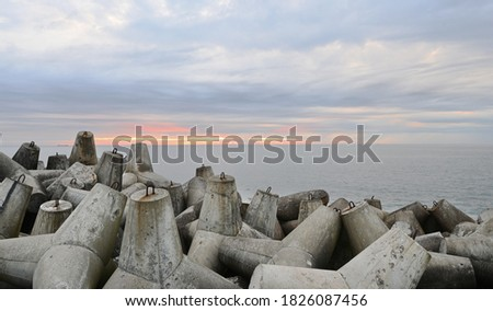 Protection of the impact of storm waves. Tetra capsules for strengthening the seashore. Breakwater on the sea coast. Concrete breakwaters. Royalty-Free Stock Photo #1826087456